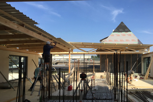 """Die Holz-Beton-Verbunddecken basieren auf Brettstapelelementen. Hier erstellen die Handwerker für die Bauzeit eine Notabdichtung aus Trapezblechen<span class=""""bildnachweis"""">Foto: Holzbau Kappler</span>"""