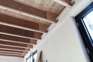 Die Holzdecken von unten: Zwischen den TJI-Stegträgern wird noch Zellulosedämmstoff eingefüllt, beplankt wird die Decke später mit Gipskartonplatten