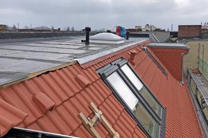"""Auf den geneigten Dachflächen verlegten die Dachdecker Ziegel, auf dem Flachdach dahinter zwei Lagen der bituminösen Abdichtung """"Vedatop Duo"""""""