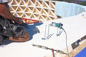Ein Handwerker verschraubt die BSH-Ringe mit den darunterliegenden, diagonalen Streben