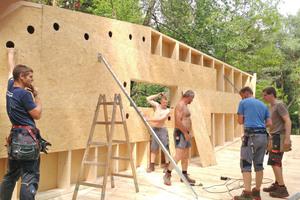 Die Holzrahmenwände, von innen beplankt mit OSB-Platten, werden später mit Zelluloseeinblasdämmstoff gefüllt