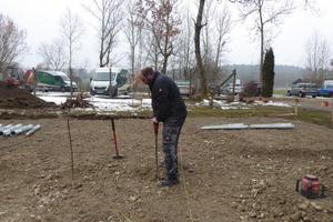 Links: Vorbereiten der Baugrube, die Standorte der Schraubfundamente werden eingemessen