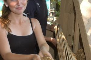 Neele Jensen, ebenfalls Architekturstudentin, füllt die Lehm-Reet-Hackschnitzel-Mischung in die Gefache