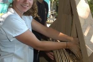 Inga Michelau, Architekturstudentin, füllt die Lehm-Reet-Hackschnitzel-Mischung in die Gefache