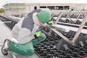 """<irspacing style=""""letter-spacing: -0.01em;"""">Ein Dachhandwerker verschraubt die Teile der Solar-Unterkonstruktion </irspacing>"""