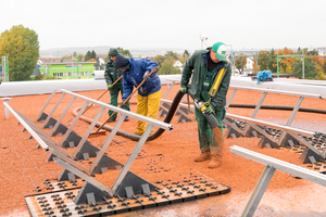 Ein Substrat für die Dachbegrüngung wird auf der Dachfläche und der Solarunterkonstruktion verteilt