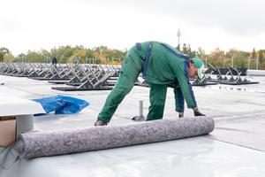Eine Faserzschutzmatte schützt die FPO-Dach- bahnen vor Beschädigungen durch die Solar-Unterkonstruktion
