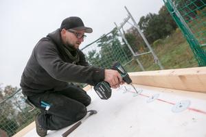"""Ein Handwerker der Firma Gottschalk platziert die """"RhinoBond""""-Halteteller. Diese werden entsprechend dem aus der Windlastberechnung und den Herstellervorschriften festgelegten Verlegemuster auf dem Dach befestigt<span class=""""bildnachweis""""></span>"""