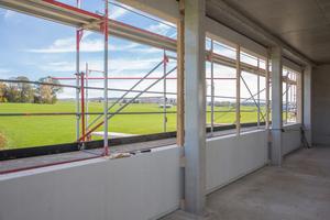 Links: Um Kabel und Leitungen zwischen Betonstützen und Holzwandelementen zu verlegen, wurden die Wände über Abstandshaltern aus Holz montiertFoto: Fermacell