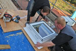 Die Handwerker setzten das quadratische Fenster auf und befestigen es seitlich an der Schürze