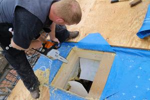 Einbau des Velux-Flachdachfensters auf einem der Zwerchhausdächer: Zunächst wird die Öffnung mit der Kettensäge ausgeschnitten⇥