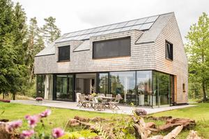 Fassade und Dachdeckung bestehen aus Alaska-Zedernholz-Schindeln. Das witterungsbeständige Material kommt ganz ohne Holzschutz aus