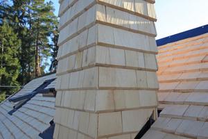 """Ein konsequenter Schritt in der Dachflächengestaltung: Dachflächen, Zwerchhäuser und sogar der Schornstein sind allesamt mit Holzschindeln eingedeckt<span class=""""bildnachweis"""">Foto: Christoph Zebe (<a href=""""http://www.zebe-pr.de"""" target=""""_blank"""">www.zebe-pr.de</a>)</span>"""