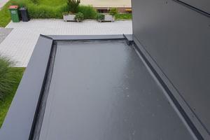 """Die Versiegelung mit """"Cryl Finish 205"""" von Triflex im unteren Dachbereich passt sich der Fassadenbekleidung des Wohnhauses an"""