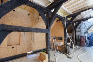 Die neue Holzrahmenkonstruktion, beplankt mit OSB-Platten, wurde hinter den historischen Fachwerkwänden eingebaut