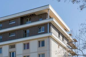 Die Fassade der aufgestockten Dachgeschosse ist mit HPL-Platten beplankt, die vertikal verlegt sind