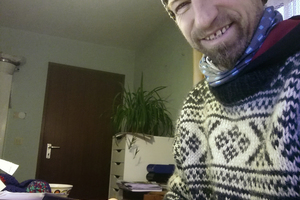 Wärmedämmung am lebenden Objekt – Redakteur bei ausgefallener Heizung mit Wollpulli und Mütze im kalten Büro Foto: Rüdiger Sinn