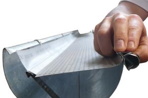 Alle 50 cm wird der Laubschutz mit einer Edelstahlklammer an der Vorderseite der Dachrinne befestigt