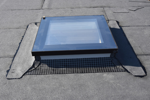 Einbau des Flachdachfensters: Gut erkennbar sind die erste, selbstklebende Abdichtungslage vorne, die ovalen Bitumenstreifen an den Ecken und die zweite Lage Bitumenbahnen an den Seiten