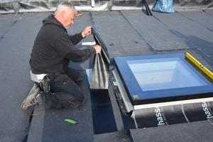 Nach dem Ausrichten wird eine selbstklebende Bitumenbahn am Übergang vom Flachdach zum Fenster aufgeklebt