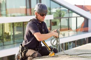 """Links oben: Ein Höhenarbeiter sichert sich für die Arbeit am Steildach am """"Lux-top FSA 2010-H""""-Schienensystem"""