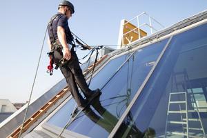 Ein Höhenarbeiter hängt sich in den Gurt und zeigt, wie belastbar das Schienensystem ist<br />