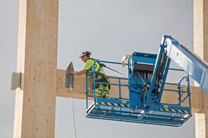 """Rechts: <irspacing style=""""letter-spacing: -0.02em;"""">Ein Arbeiter verschraubt große Stahlplatten für die Aufnahme von Querstreben an der Holzkonstruktion</irspacing>"""