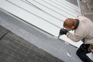 Rechts: Die Dachdecker befestigen die Schare mit Fest- und Schiebehaften