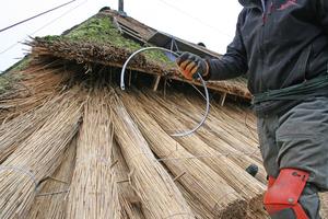 Bei der gebundenen Deckung arbeitet der Reetdachdecker mit einer Rundnadel, die er unter dem Reet um eine Dachlatte führt