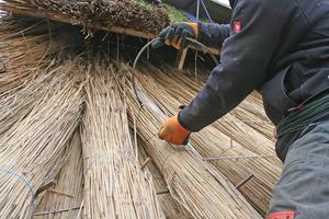 In einer Öse an der Rundnadel wird der Draht eingehängt, dann wird die Nadel einmal um die Latte geführt und so der Draht um die Latte gelegt