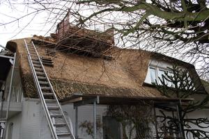 Der Arbeitsplatz der Reetdachdecker: In der roten Transportbox lagern Reetbunde, die per Kran auf das Dach gehoben wurden