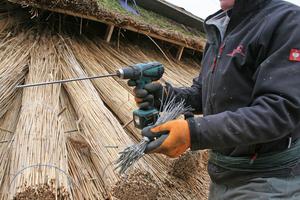 Bei der geschraubten Deckung werden die Reetbunde mit Drahtschrauben und Akkuschrauber befestigt