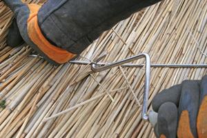 """<irspacing style=""""letter-spacing: -0.02em;"""">Dann wird der Draht mit einem Dreher an der Stange festgedreht – das Reet sitzt jetzt fest auf dem Dach</irspacing>"""