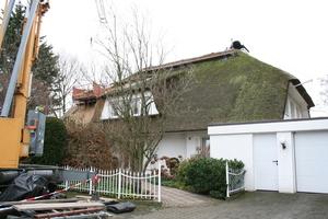 Die Vorderseite des Hauses während der Ausbesserung, an der rechten Seite noch mit Moos bewachsen