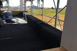 Insgesamt wurden 44 Balkone mit EPDM abgedichtet. Der Kleber wird mit dem Sprühgerät aufgebracht  Foto: Carlisle  <br /> <br /> <br />