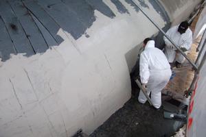 """Auf die mit Bitumenbahnen abgedichteten Flächen bringen die Dachdecker eine erste Schicht Flüssigkunststoff auf  <span class=""""bildnachweis"""">Foto: Triflex</span>"""
