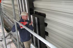 Rechts: Über die Metallschienen wird die erste Dämmschicht an den Wänden verschraubt