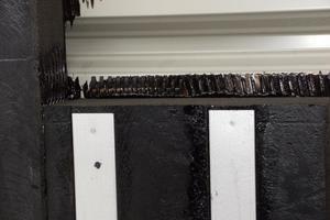 Im Wandbereich werden die Dämmplatten mit Bitumenkaltkleber verklebt und mechanisch befestigt, hier die erste Dämmschicht