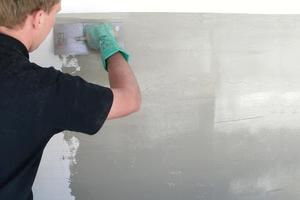 """Rechts: Abschließend tragen die Handwerker die Versiegelung """"Triflex Cryl Finish 205"""" in Weiß auf"""