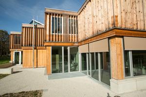 Die Holzstützen, die das Gebäude tragen, sind von außen an der Fassade des Erdgeschosses erkennbar