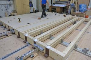Hohlkastenelemente aus KVH, vorgefertigt und gedämmt bei Grossmann Bau in Rosenheim, wurden in die Tragkonstruktion aus Brettschichtholz eingefügt