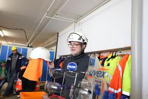 Dieter Terner, Leiter des BG Bau-Praxiszentrums in Nürnberg, zeigt einen Helm mit Nackenschutz, der vor Sonne und UV-Strahlung schützt