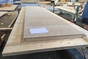 Vorfertigung der Akustikplatte im Werk bei Holzbau Amann. Auf eine Brettsperrholzplatte werden Akustikplatten eingesetzt. Zusätzlich sind die Platten mit Mineralwolle gedämmtFoto: Holzbau Amann