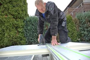 """Thomas Straub von der Dachdeckerfirma Karl Stahl GmbH aus Sigmaringen schneidet eine alukaschierte PIR-Dämmstoffplatte mit der Dämmstoffsäge """"ISC 240"""" von Festool"""