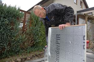 """Thomas Straub von der Dachdeckerfirma Karl Stahl Bedachungen aus Sigmaringen schrägt einen alukaschierten PIR-Dämmstoff im Freischnitt an <span class=""""bildnachweis"""">Foto: Rüdiger Sinn</span>"""