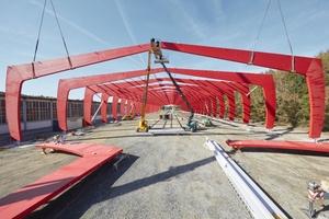 Die Spannweite der zusammengesetzten Rahmen beträgt über 45 MeterRechts: Ein Stahlbauteil für den Anschluss des BSH-Rahmens an den Fußpunkt wird montiert