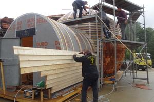 Vorne wird die Bretterschalung montiert, hinten die gebogenen Fichtenholzlatten als Unterkonstruktion für die Schindeln