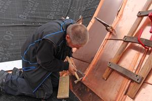 Spengler Bodo Langohr beim Anarbeiten des Kupferbleches in einer der Lagerkehlen