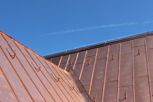 Übergang von einer der Lagerkehlen zum Hauptdach: Die Dachhaken zum Anlegen von Dachdeckerleitern sind mit Schrauben unterhalb der Kupferbleche befestigt