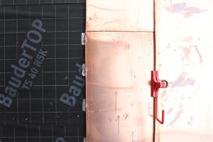 Rechts: Die Kupferschare sind mit Schiebehaften befestigt. Der rote Haken dient dem Anlegen von Dachdeckerleitern in der Bauzeit
